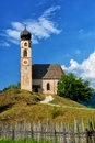 Beautiful church in italian alps a the with a crude stick fence and a lovely onion dome typical of the german austrian influence Royalty Free Stock Image