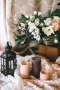 Beautiful composition of pink candles, vintage candlestick colors and white lace. Wedding decor in rustic style Royalty Free Stock Photo