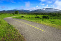 Beautiful countryside road in green field under blue sky chiang mai thailand Stock Photo