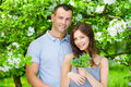 Beautiful couple embracing near flowered tree in the park girl hands flowers concept of love and stable relations Royalty Free Stock Photography