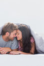 Beautiful couple head against head under the duvet in bed Stock Image