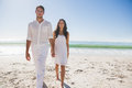 Beautiful couple holding hands and walking towards camera at the beach Royalty Free Stock Images