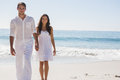 Beautiful couple holding hands and walking towards camera at the beach Stock Photography