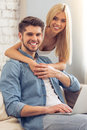 Beautiful couple at home with gadget is looking camera and smiling sitting man is using a laptop while his girlfriend is hugging Royalty Free Stock Photo