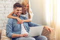 Beautiful couple at home with gadget smiling man is using a laptop while his girlfriend is hugging him Stock Photography
