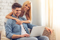 Beautiful couple at home with gadget smiling man is using a laptop while his girlfriend is hugging him Royalty Free Stock Photo