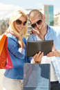 Beautiful couple shopping online young using a digital tablet for outdoors on a sunny day Royalty Free Stock Image