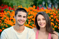 Beautiful couple smiling next to a flower background young on hot summer day Royalty Free Stock Photo