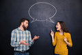 Picture : Beautiful couple talking over blackboard background with speech bubble travel