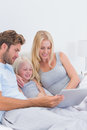 Beautiful couple using a laptop with their daughter Royalty Free Stock Photo