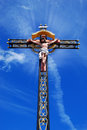 Beautiful cross with jesus christ roadside against blue sky Stock Photos