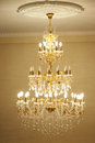 Beautiful crystal chandelier ancient in a hall lamp with soft yellow light Royalty Free Stock Photos
