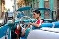 Beautiful Cuban woman in the classical American car