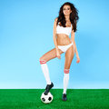 Beautiful curvy brunette posing with a soccer ball long shapely tanned legs in white lingerie and boots on green and blue Stock Image