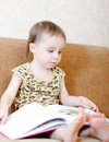 Beautiful cute baby reading book sitting couch Stock Image