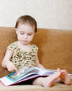 Beautiful cute baby reading book sitting couch Royalty Free Stock Photo