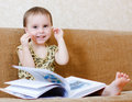 Beautiful cute baby reading a book while sitting on the couch Royalty Free Stock Photography