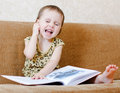 Beautiful cute baby reading a book while sitting on the couch Royalty Free Stock Photos