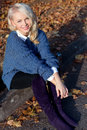 Beautiful cute blonde girl in a blue jacket sitting on the road in the autumn Park Royalty Free Stock Photo