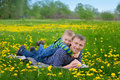 Beautiful cute boy in the park blowing on dandelion spring time Royalty Free Stock Photo