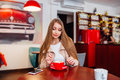 Beautiful cute girl in the cafe with coffee smiling .Portrait of young gorgeous female drinking coffee and looking with smile out Royalty Free Stock Photo