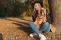 Beautiful cute happy girl in a black hat playing with her dog in a park in autumn another sunny day Royalty Free Stock Photo