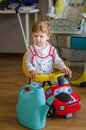 Beautiful cute little boy riding sport toy car a at home Stock Image