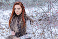 Beautiful cute young girl with red hair walking in a snowy forest among the trees missed first trimester bushes with red yago Royalty Free Stock Photo