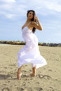 Beautiful dancer posing on the beach good looking female model with white dress Stock Photography
