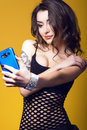 Beautiful dark haired girl with tattoo on her arm holding a blue cell phone and making selfie Royalty Free Stock Photo