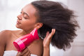 Beautiful dark skinned girl in white towel blowing dry her hair with rose hairdryer isolated on background closing eyes Royalty Free Stock Photos