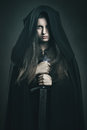 Beautiful dark woman with black robe and sword Royalty Free Stock Photo