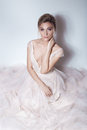 Beautiful delicate bride sexy girl in soft pink skazachno wedding dress with a cut on the chest and back with makeup and evening h Royalty Free Stock Photo