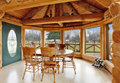 Beautiful dining room in log cabin house bright with floor to ceiling windows rustic table set and cathedral ceiling with beams Royalty Free Stock Photos