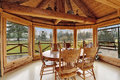 Beautiful dining room in log cabin house bright with floor to ceiling windows rustic table set and cathedral ceiling with beams Royalty Free Stock Photo
