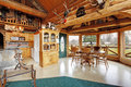 Beautiful dining room in log cabin house view of kitchen and area furnished with wooden cabinets rustic table set Stock Photos