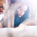 Beautiful ebony girl laying on bed holding mirror sexy with lens flare Royalty Free Stock Images