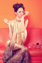 Beautiful elegant lady trying out perfumes on couch Royalty Free Stock Photo
