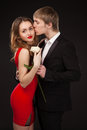 Beautiful elegant love couple wearing suit red dress white rose studio over black background Stock Images
