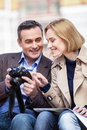 Beautiful elegant mid age couple resting outdoors man holding camera and showing pictures to blond woman Stock Images