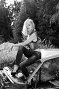 Beautiful elegant sexy girl blonde in jeans in black shoes sits on the old car in the forest Royalty Free Stock Photo