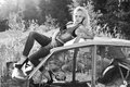 Beautiful elegant sexy girl blonde in jeans in black shoes sits on the old car in the forest Stock Images