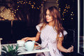 Beautiful elegant woman having breakfast drinking coffee and eating cake in city cafe Royalty Free Stock Photo