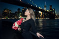 Beautiful elegant woman holding bouquet of rose flower wearing black evening dress in the city Royalty Free Stock Photo