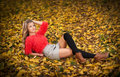 Beautiful elegant woman with red blouse and short skirt posing in park during fall. Young pretty woman with blonde hair lying down