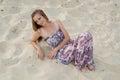 Beautiful elegant woman sit on sand Royalty Free Stock Photo