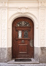 Beautiful end portal in center munich elegant wooden door with bronze handle and decorations framed by elaborated stucco columns Stock Image