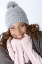 Beautiful ethnic girl smiling in winter outfit happily wearing hat Stock Image