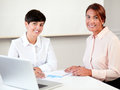 Beautiful executive women smiling at you portrait of while sitting on office desk Royalty Free Stock Photo