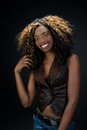 Beautiful exotic african american woman with a lovely natural sm smile wearing jeans against dark background Stock Images